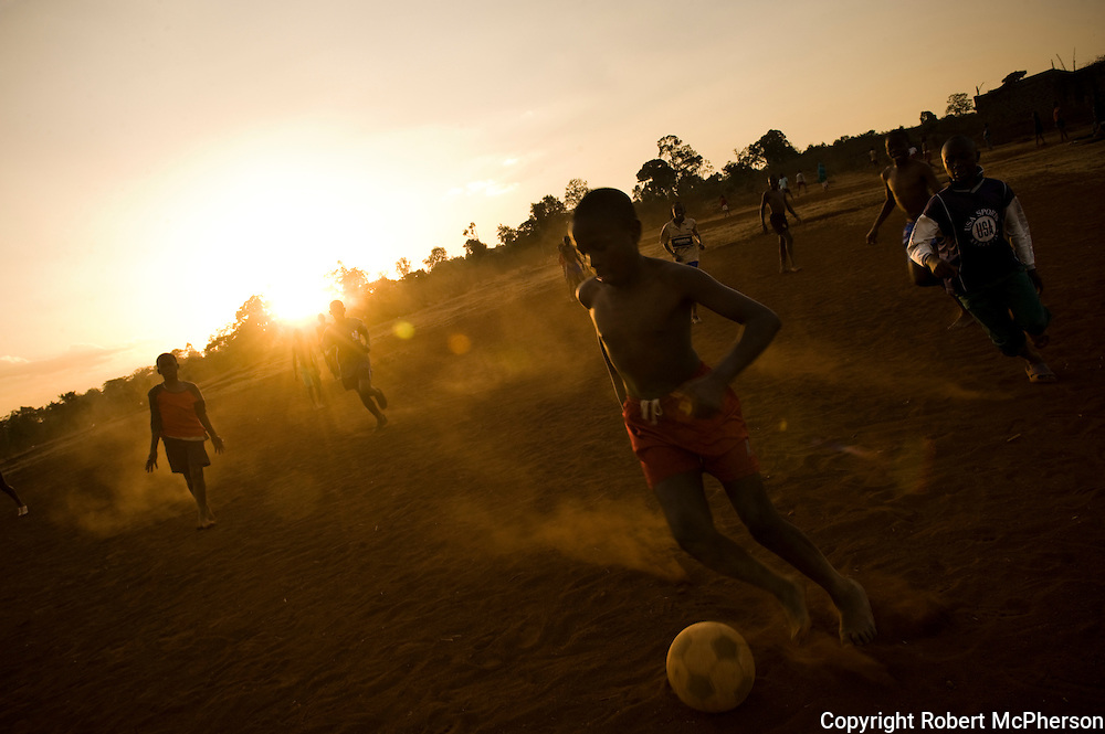 KENYA. Nairobi. Kids playing football in the slum of Kibera.Their trainer was 18 years old and recruited young children to play football instead of using drugs.The team had no money for football shoes...Kibera is Africa's largest slum and it is located in Nairobi, Kenya. It houses one million people squeezed into less than a square mile.