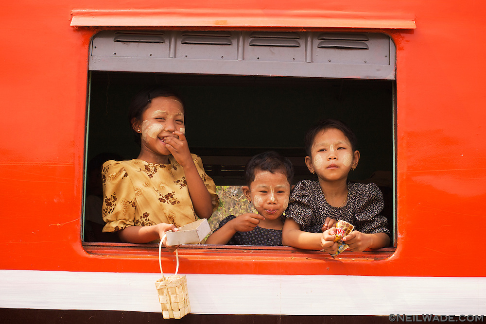 Friendly Burmese minority girls on a train. The girls are wearing thanaka, a common makeup used by women and children.  Myanmar (Burma)