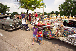 Stock photo of children standing beside a colorfully decorated car