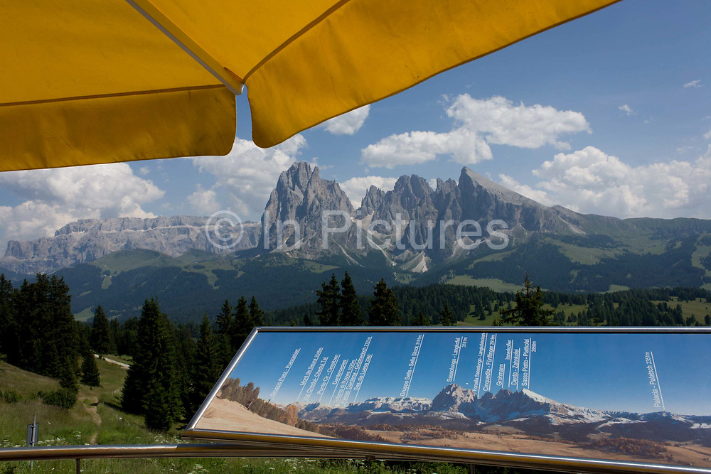 Cable car terrace panaorama above the Siusi plateau, above the South Tyrolean town of Ortisei-Sankt Ulrich in the Dolomites, Italy. Walkers can enjoy panoramic views of the peaks like Sassalungo that envelope the location. The Alpe di Siusi is the biggest high-alpine pasture in Europe with a surface of 57 km² and its altitude range from 1680 to 2350 m above sea level. This high-alpine pasture is located in the heart of the Dolomites surrounded by the Sasso Lungo Mountain Group, the Sciliar Nature Park, and the Catinaccio Mountain Group, the Northern Alps and the Sciliar Mountain Massif with Santner Peak.