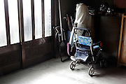 elderly wheeled walking support and sitting card standing by the entrance door