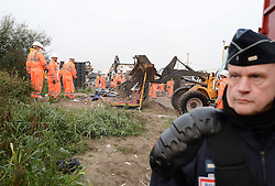 """A French police officer stands guard as a large crew of demolition workers start breaking down living areas of the """"Jungle"""" migrant camp, close to Calais in northern France."""