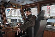 Sean Hovik sits in the captains chair in the wheelhouse of his 59-foot seine fishing vessel Shemya Monday, Jan. 6, 2020 at Daly Float in Ketchikan, Alaska