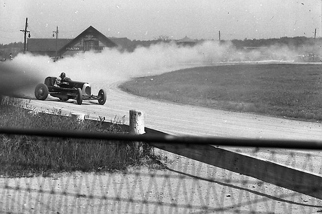 Photographer Ozzie Lyons took advantage of what thin protection was available when he shot this racer getting maximum drive off the corner.