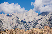 Mount Whitney (14,505 feet or 4421 m elevation) is the highest summit in the contiguous United States and the Sierra Nevada. Photographed from Alabama Hills BLM Recreation Area on the eastern side of the Sierra Nevada Mountains in the Owens Valley, west of Lone Pine in Inyo County, California, USA. The Alabama Hills are a popular filming location for television and movie productions. Two main types of rock are exposed at Alabama Hills: 1) orange, drab weathered metamorphosed volcanic rock 150-200 million years old; and 2) 82- to 85-million-year-old biotite monzogranite which weathers to potato-shaped large boulders.