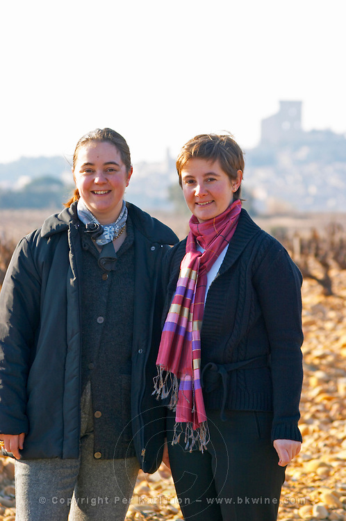Gaelle and Amelie (right) Barrot owners of Chateau des Fines Roches in the vineyard in Chateauneuf-du-Pape, the village in the background, Vaucluse, Rhone, Provence, France