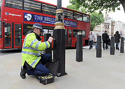 © under license to London News Pictures. LONDON, UK  17/05/2011. A police officer checks a lamp post outside Downing Street before placing a security seal on it. Police carry out security checks in Whitehall, Central London today (17 May 2011). Please see special instructions for usage rates. Photo credit should read Stephen Simpson/LNP.