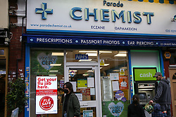 © Licensed to London News Pictures. 13/10/2020. London, UK. A woman wearing a face covering walks past a 'Flu Jab' advert in a pharmacist window in north London. According to research, a flu jab  could offer some vital protection against Covid-19. GPs and pharmacies are to vaccinate almost 30 million people in England against flu in the next two months to help prevent the health service collapsing under the joint burden of a flu outbreak and Covid-19. Photo credit: Dinendra Haria/LNP