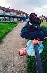 Boy playing next to shops on run down estate Bradford Yorkshire UK