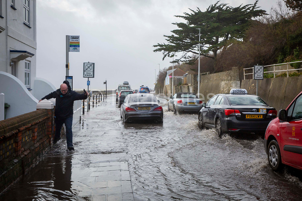 People walking down the A259 between Folkestone and Hythe which is flooded at Sandgate, Kent on the south coast of England, as Storm Ciara continues to sweep over the country on February 10th 2020 in Folkestone, United Kingdom. Amber weather warnings were put into place by the MET office as gusts of up to 90mph and heavy rain swept across the UK. An amber warning from the MET office expects a powerful storm that will disrupt air, rail and sea links travel, cancel sports events, cut electrical power and damage property.