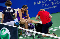 Jelena Jankovic of Serbia is assisted after injury of her left ankle during play against Anastasiya Yakimova of Belarus  at 2nd Round of Singles at Banka Koper Slovenia Open WTA Tour tennis tournament, on July 22, 2010 in Portoroz / Portorose, Slovenia. (Photo by Vid Ponikvar / Sportida)