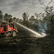 After a vast forest fire, a firefighting truck hoses a mix of pressured water and wetting agent deep into the ground. The lower part of the humus is still smoldering and ejecting smoke and CO2, so it's important to reach deep in the ground.