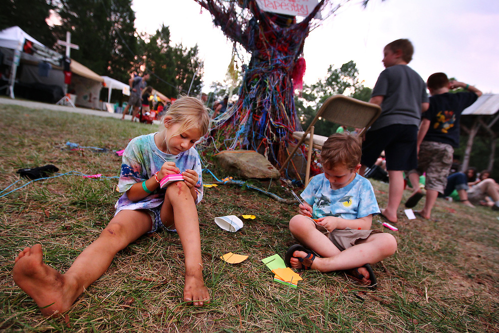 Children weave their prayers into the tapestry woven around a tree at the Wild Goose Festival at Shakori Hills in North Carolina June 24, 2011.  (Photo by Courtney Perry)