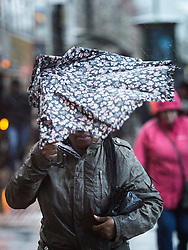 © Licensed to London News Pictures . 19/12/2014 .  Manchester , UK . Umbrellas are turned inside out as fast gusts of wind and icy rain slices down on pedestrians in Piccadilly in Manchester City Centre this afternoon (Friday 19th December 2014) . Photo credit : Joel Goodman/LNP