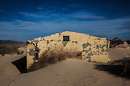 An abandoned home buried by sand in the Mojave desert near Barstow.<br /> U.S. Route 66, also known as the Mother Road, in the Mojave desert of California. The two major connector cites in the Mojave desert are Barstow and Amboy. U.S. Route 66 was the first major east west highway for the US, starting in Chicago, Il and ending in Santa Monica, CA. The 2,448 mile long highway was built in November 11,1926. Most of Route 66 has been decommissioned, but there are several parts that are now historically preserved.