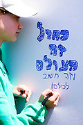 """Israel, Caesarea, Children activity to promote clean seas and oceans Organised by the Green Net foundation May 6 2009 Children writing ecological slogans on a white board. """"Blue is the world and it is important to all of us"""""""