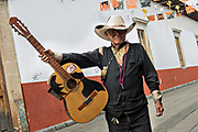 An elderly cowboy musician poses with his guitar in Uruapan, Michoacan, Mexico.