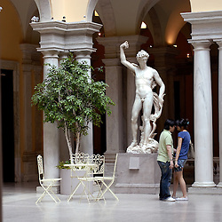 A couple flirts near a classic European statue in the European art and sculpture court of the Walter's Art Museum in Baltimore, Maryland...Photo by Susana Raab