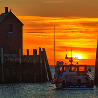 Massachusetts sunrise photo of the famous red fishing shack Motif Number One in Rockport, MA on Cape Ann at sunset. The historic landmark is known throughout New England as Motif Number One because it is the most often painted building in America.<br />