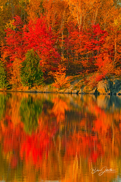 Autumn colour reflected in Simon Lake at dawn, Greater Sudbury, Ontario, Canada