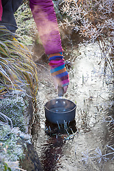 Melting ice on a frozen pond using a saucepan of boiling water
