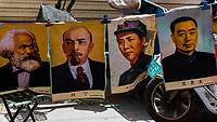 Old propaganda posters of Marx, Lenin, Mao and Chou En Lai for sale at a street market in the bazaar in Kashgar, an oasis city in Xinjiang Province, China.  It is the westernmost city in China, located near the border with Afghanistan, Kyrgyzstan, Pakistan, and Tajikistan. It was a stop on the Silk Road. Uyghur people are a Central Asian people of Muslim Turkic origin. They are China's largest minority group.