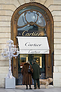 Stylish couple with dog look in Cartier shop window in Place Vendome, Central Paris, France