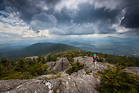 Female trail runner (Katy Farber) ascends a rocky ridge along the spine of the Green Mountains in Vermont as a storm closes in.  Views of Burnt Rock looking south from White Rocks summit, Putnam State Forest ,Patterson Brook Project