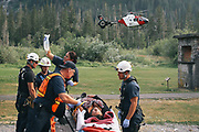 Rescue workers treat a victim before she was airlifted to Harborview Medical Center, Monday, July 6, 2015 at the Big Four trail head.  One person died and five were injured after the Big Four ice caves collapsed on hikers.
