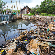 CAPTION: A build-up of rubbish next to a fishpond in Tapak. Each time it floods, large amounts of waste are deposited from upstream. Over time, this clogs the river up and worsens the severity of flooding. LOCATION: Tapak, Semarang, Indonesia. INDIVIDUAL(S) PHOTOGRAPHED: N/A.