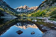 The Maroon Bells and yellow aspen leaves reflect in Maroon Lake at sunrise. The Maroon Bells are two adjacent peaks of the Elk Mountains: Maroon Peak 14,163 feet on left, seen behind North Maroon Peak 14,019 feet, in Maroon Bells-Snowmass Wilderness of White River National Forest. The mountains are on the border between Pitkin County and Gunnison County, about 12 miles southwest of Aspen, in Colorado, USA.