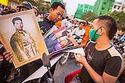"29 JANUARY 2013 - PHNOM PENH, CAMBODIA:  Vendors sell photos of late Cambodian King Norodom Sihanouk in front of the Royal Palace in Phnom Penh. Sihanouk (31 October 1922 - 15 October 2012) was the King of Cambodia from 1941 to 1955 and again from 1993 to 2004. He was the effective ruler of Cambodia from 1953 to 1970. After his second abdication in 2004, he was given the honorific of ""The King-Father of Cambodia."" Sihanouk held so many positions since 1941 that the Guinness Book of World Records identifies him as the politician who has served the world's greatest variety of political offices. These included two terms as king, two as sovereign prince, one as president, two as prime minister, as well as numerous positions as leader of various governments-in-exile. He served as puppet head of state for the Khmer Rouge government in 1975-1976. Most of these positions were only honorific, including the last position as constitutional king of Cambodia. Sihanouk's actual period of effective rule over Cambodia was from 9 November 1953, when Cambodia gained its independence from France, until 18 March 1970, when General Lon Nol and the National Assembly deposed him. Upon his final abdication, the Cambodian throne council appointed Norodom Sihamoni, one of Sihanouk's sons, as the new king. Sihanouk died in Beijing, China, where he was receiving medical care, on Oct. 15, 2012. His cremation is scheduled to take place on Feb. 4, 2013. Over a million people are expected to attend the service.      PHOTO BY JACK KURTZ"
