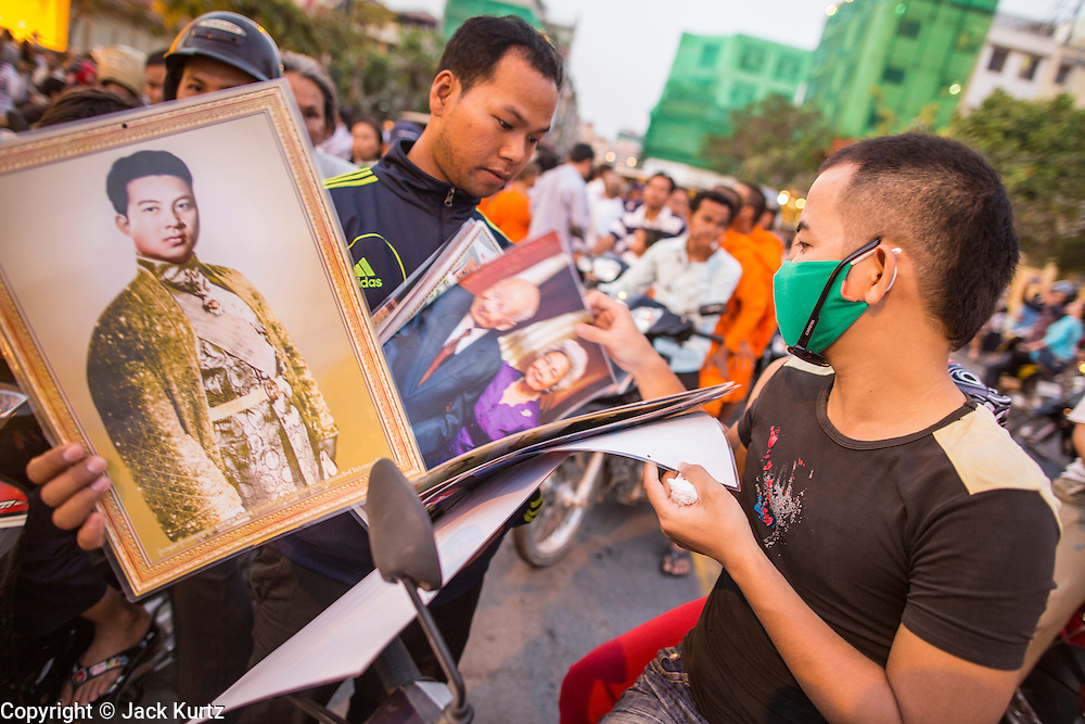 """29 JANUARY 2013 - PHNOM PENH, CAMBODIA:  Vendors sell photos of late Cambodian King Norodom Sihanouk in front of the Royal Palace in Phnom Penh. Sihanouk (31 October 1922- 15 October 2012) was the King of Cambodia from 1941 to 1955 and again from 1993 to 2004. He was the effective ruler of Cambodia from 1953 to 1970. After his second abdication in 2004, he was given the honorific of """"The King-Father of Cambodia."""" Sihanouk held so many positions since 1941 that the Guinness Book of World Records identifies him as the politician who has served the world's greatest variety of political offices. These included two terms as king, two as sovereign prince, one as president, two as prime minister, as well as numerous positions as leader of various governments-in-exile. He served as puppet head of state for the Khmer Rouge government in 1975-1976. Most of these positions were only honorific, including the last position as constitutional king of Cambodia. Sihanouk's actual period of effective rule over Cambodia was from 9 November 1953, when Cambodia gained its independence from France, until 18 March 1970, when General Lon Nol and the National Assembly deposed him. Upon his final abdication, the Cambodian throne council appointed Norodom Sihamoni, one of Sihanouk's sons, as the new king. Sihanouk died in Beijing, China, where he was receiving medical care, on Oct. 15, 2012. His cremation is scheduled to take place on Feb. 4, 2013. Over a million people are expected to attend the service.      PHOTO BY JACK KURTZ"""