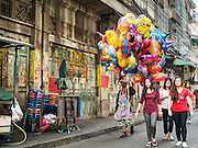 """07 FEBRUARY 2016 - BANGKOK, THAILAND: A man selling inflatable toys for Chinese New Year walks down a street in Bangkok's Chinatown neighborhood. Chinese New Year, also called Lunar New Year or Tet (in Vietnamese communities) starts Monday February 8. The coming year will be the """"Year of the Monkey."""" Thailand has the largest overseas Chinese population in the world; about 14 percent of Thais are of Chinese ancestry and some Chinese holidays, especially Chinese New Year, are widely celebrated in Thailand.        PHOTO BY JACK KURTZ"""