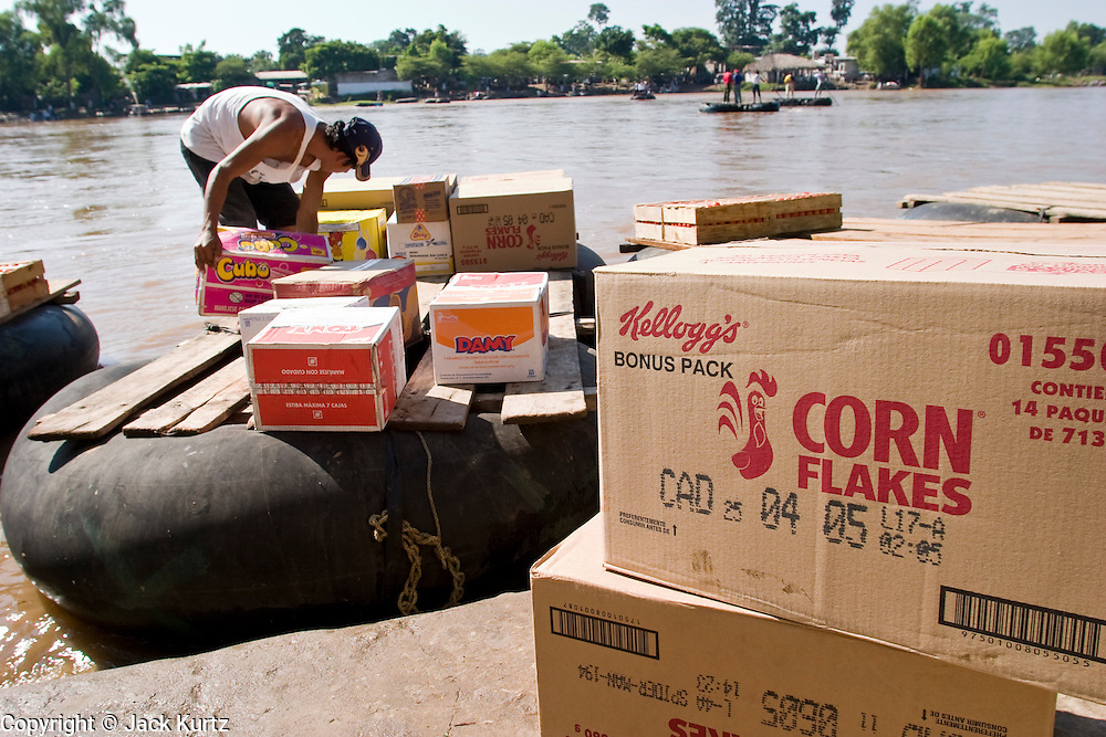 26 JULY 2004 -- TAPACHULA, CHIAPAS, MEXICO:  A raft operator (balsero) in Hidalgo, Mexico, about 20 miles from Tapachula, loads his raft with corn flakes he is smuggling to Guatemala. Tapachula is center of the smuggling industry between Mexico and Guatemala. Consumer goods are smuggled south to Guatemala (to avoid paying Guatemalan import duties) and people are smuggled north into Mexico. Most of the people coming north are hoping to eventually get to the United States. PHOTO BY JACK KURTZ