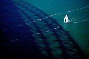Small sailing boat approaches the shadow of the Sydney Harbour Bridge. Sydney, Australia