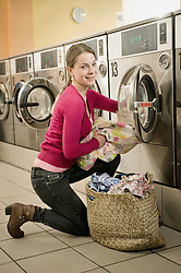 Young woman filling up cloths in machine, smiling