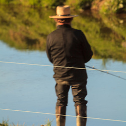 Lititz, PA, USA - April 4, 2013: An Amish man fishes in a stream in Lancaster County, PA