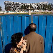 """A passer-by covers herself from dust as she walks past the """"Bird's Nest"""" National Stadium, which will be unveiled for the 2008 Summer Olympics. Beijing is one of the most air-polluted cities on earth."""
