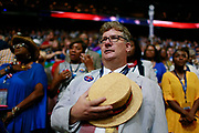 07252016 - Philadelphia, Pennsylvania, USA: A Hillary Clinton supporter removes his hat for the National Anthem during roll call on the second day of the Democratic National Convention. (Jeremy Hogan/Polaris)
