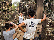 "14 MARCH 2105 - SIEM REAP, SIEM REAP, CAMBODIA: Tourists photograph each other in the Bayon, one of the temples in Angkor Thom, a part of the Angkor Wat complex. Bayon was built in 12th or 13th century CE. The area known as ""Angkor Wat"" is a sprawling collection of archeological ruins and temples. The area was developed by ancient Khmer (Cambodian) Kings starting as early as 1150 CE and renovated and expanded around 1180CE by Jayavarman VII. Angkor Wat is now considered the seventh wonder of the world and is Cambodia's most important tourist attraction.   PHOTO BY JACK KURTZ"