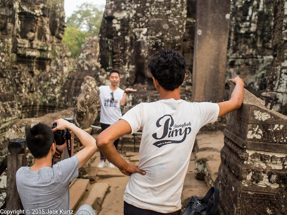 """14 MARCH 2105 - SIEM REAP, SIEM REAP, CAMBODIA: Tourists photograph each other in the Bayon, one of the temples in Angkor Thom, a part of the Angkor Wat complex. Bayon was built in 12th or 13th century CE. The area known as """"Angkor Wat"""" is a sprawling collection of archeological ruins and temples. The area was developed by ancient Khmer (Cambodian) Kings starting as early as 1150 CE and renovated and expanded around 1180CE by Jayavarman VII. Angkor Wat is now considered the seventh wonder of the world and is Cambodia's most important tourist attraction.   PHOTO BY JACK KURTZ"""
