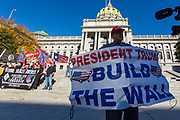 """Harrisburg, PA -- Arthur Jones, wearing a Make America Great Again hat, holds a sign reading """"President Trump Build the Wall"""" at a 2016 rally of white supremacists at the Pennsylvania State Capitol."""