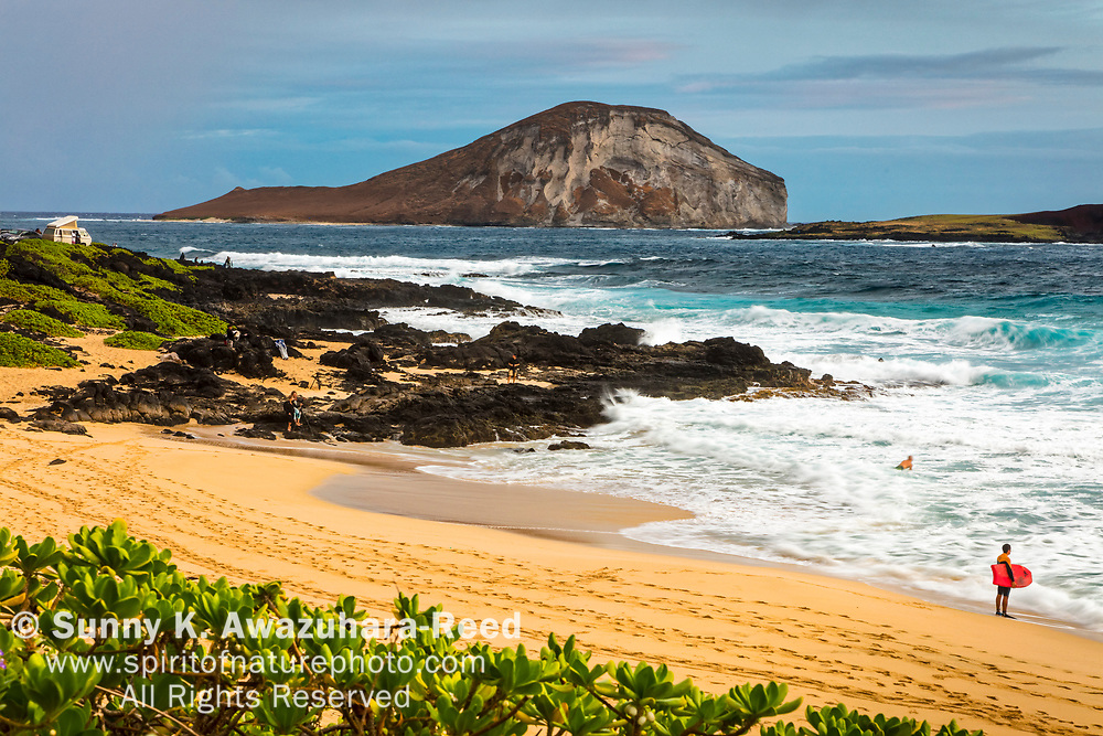 A surfer at Makapu'u Beach. Rabbit Island in the background. Oahu Island, Hawaii.