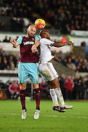 James Collins of West Ham jumps for a header with Andre Ayew of Swansea city. Barclays Premier league match, Swansea city v West Ham Utd at the Liberty Stadium in Swansea, South Wales  on Sunday 20th December 2015.<br /> pic by  Andrew Orchard, Andrew Orchard sports photography.