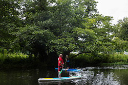 Denham, UK. 13 July, 2020. A man and a woman practise water sport in front of an ancient alder tree alongside the river Colne which lies close to HS2 ground clearance work at Denham Ford in the Colne Valley.