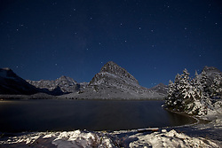 Swiftcurrent Lake under the stars, Mt. Grinnell towers over the lake as it reaches into the night sky.