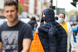 © Licensed to London News Pictures. 16/05/2021. London, UK. A woman covers half of her face as she is caught in the rain in north London. More rain is forecast for the South East of England this week. Photo credit: Dinendra Haria/LNP