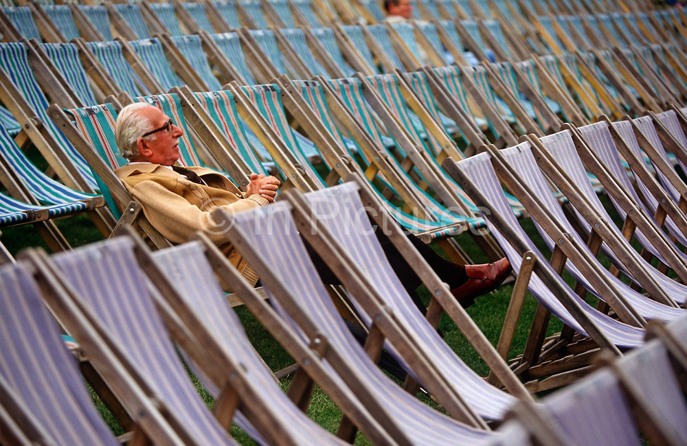 A lone pensioner sits in one deckchair among many before an outside concert at Kenwood House, North London. Set in leafy grounds beside Hampstead Heath, these grounds were remodelled by Robert Adam between 1764 and 1779. English Heritage host Summer concerts here and families and music fans spend war summer evenings listening to opera, classical or series of themed performances by visiting artists and groups. Here is also the source of one of London's lost rivers, The Fleet which rises here and flows downhill into the city where it becomes part of the sewer system, emerging in the Thames at Blackfriars.