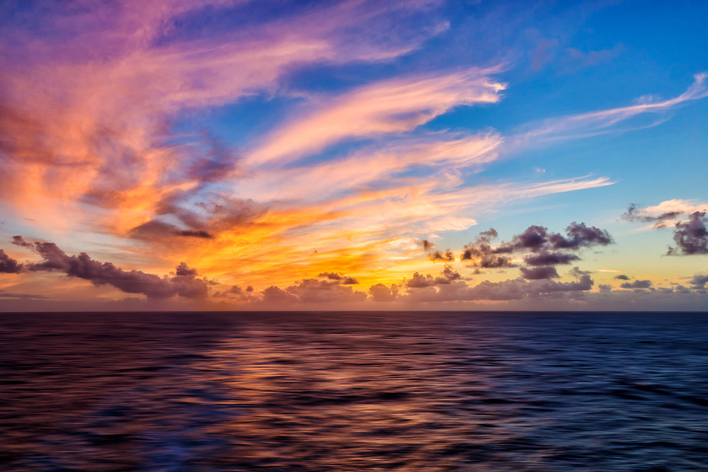 Wispy clouds meet the seas just off the coast of Maui at Sunset.